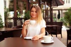 Mooie vrouw het drinken koffie bij koffie stock afbeeldingen