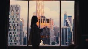 Mooie vrouw het drinken koffie door het venster met verbazende cityscape mening tijdens zonsondergang royalty-vrije stock afbeeldingen