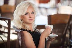 Mooie vrouw het drinken koffie in koffierestaurant, meisje in bar, de zomervakantie. Vrij blond bij ontbijt. gelukkige glimlachend Royalty-vrije Stock Foto