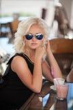 Mooie vrouw het drinken koffie in koffierestaurant, meisje in bar, de zomervakantie. Vrij blond bij ontbijt. gelukkige glimlachend Royalty-vrije Stock Foto's