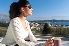Mooie vrouw het drinken koffie of thee op balkon met mooi landschapspanorama stock foto