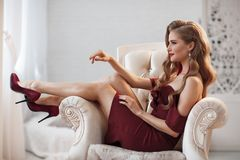 Mooie vrouw in het elegante openluchtkleding alleen stellen die, als voorzitter zitten Royalty-vrije Stock Afbeelding