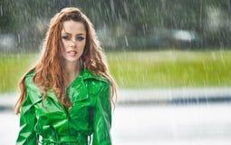 Mooie vrouw in het heldergroene laag stellen in de regen Stock Afbeelding