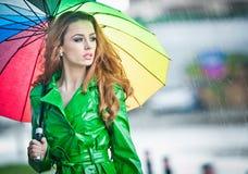 Mooie vrouw in het heldergroene laag stellen in de regen die een multicolored paraplu houden Royalty-vrije Stock Afbeelding