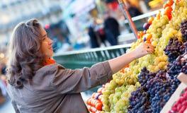 Mooie vrouw het kopen druiven Stock Afbeeldingen