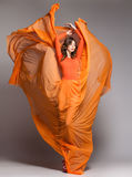Mooie vrouw in het lange oranje kleding dramatisch stellen Royalty-vrije Stock Foto