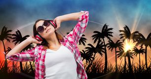 Mooie vrouw het luisteren muziek door hoofdtelefoons terwijl status tegen silhouetbomen Stock Fotografie