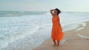 Mooie vrouw in het oranje kleding en zonglazen stellen die zich op het natte zandige strand op de achtergrond van het overzees be stock videobeelden