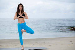 Mooie vrouw het praktizeren yoga bij strand Royalty-vrije Stock Foto