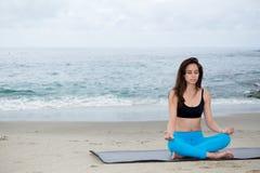 Mooie vrouw het praktizeren yoga bij strand Stock Afbeeldingen