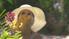 Mooie vrouw het snuiven aroma bloeiende bloemen in de zomertuin Meisje die in hoed van geur van bloeiende orchideeën binnen genie stock video