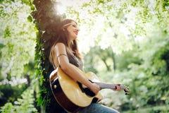 Mooie vrouw het spelen gitaar in aard Royalty-vrije Stock Foto's