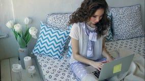 Mooie vrouw het typen tekst op een laptop zitting op een bed in een comfortabele ruimte stock footage