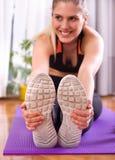 Mooie vrouw het uitrekken zich benen op vloer na training royalty-vrije stock fotografie