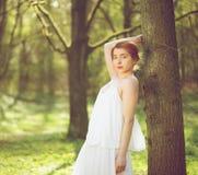 Mooie vrouw in het witte kleding stellen in bos royalty-vrije stock foto