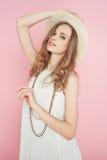 Mooie vrouw in het witte kleding stellen op roze achtergrond in hoed Stock Afbeeldingen