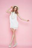Mooie vrouw in het witte kleding stellen op roze achtergrond in hoed Stock Afbeelding