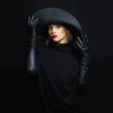 Mooie vrouw in hoed en leerhandschoenen mannequinmeisje die zwarte hoed proberen De heks van Halloween Royalty-vrije Stock Foto