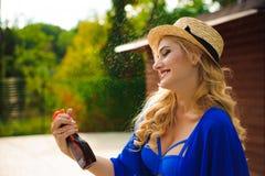 Mooie vrouw in hoedenzitting dichtbij een pool en het toepassen van zonneschermnevel op haar lichaam stock fotografie