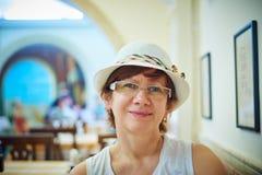 Mooie vrouw in hoedenzitting in koffie stock afbeelding