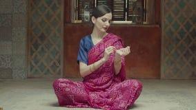 Mooie vrouw in Indische Sari die olieparfum gebruiken stock videobeelden