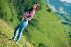 Mooie vrouw in jeans die zich op het gras bevinden stock afbeeldingen