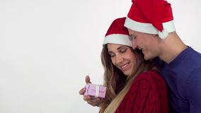 Mooie vrouw in Kerstmishoed ontvangen huidig van haar vriend stock videobeelden