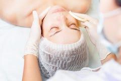 Mooie vrouw in kuuroordsalon die gezichtsbehandeling, schoonheidsconcept ontvangen Royalty-vrije Stock Afbeelding
