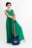 Mooie vrouw in lange groene kleding met gitaar stock foto's