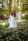 Mooie vrouw in lange witte kleding die zich in een bos bevinden Stock Fotografie