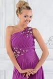 Mooie vrouw in lilac lange kleding in wit binnenland. stock foto