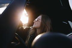 Mooie vrouw in manier convertibele auto op zonsondergang royalty-vrije stock afbeeldingen
