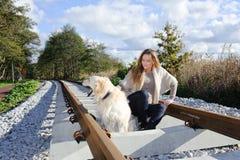 Mooie vrouw met aardige hond bij spoorwegen Royalty-vrije Stock Foto's