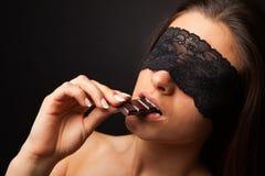 Mooie vrouw met blinddoek sexy het eten chocolade Stock Afbeeldingen