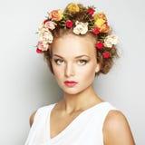 Mooie vrouw met bloemen. Perfecte gezichtshuid. Schoonheidsportret Stock Foto