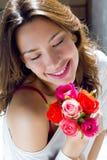 Mooie vrouw met bloemen thuis stock afbeelding