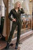 Mooie vrouw met blond haar in vrijetijdskleding die op de straat dichtbij koffie stellen royalty-vrije stock foto's