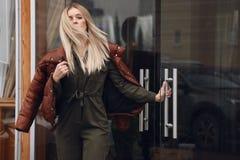 Mooie vrouw met blond haar in vrijetijdskleding die op de straat dichtbij koffie stellen stock afbeelding