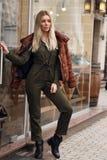 Mooie vrouw met blond haar in vrijetijdskleding die op de straat dichtbij koffie stellen stock fotografie