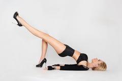 Mooie vrouw met blond lang haar die op haar terug op de grond in sexy positie liggen Stock Foto's