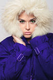 Mooie vrouw met bontkap. de winter modieus meisje in blauwe laag Royalty-vrije Stock Foto's