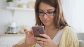 Mooie vrouw met bruin haar, in glazen en het gele cardigan texting aan haar vrienden stock videobeelden