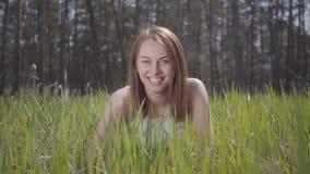 Mooie vrouw met bruin haar in het groene gras rond het spectaculaire bos lachen stock videobeelden