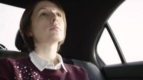 Mooie vrouw met bruin haar in witte blouse en het kastanjebruine sweater berijden in auto en het bekijken venster stock footage