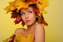 Mooie vrouw met de herfstbladeren op geel Stock Afbeelding