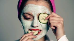 Mooie vrouw met de komkommerplakken van het moddermasker Mooi meisje die een plak van komkommer voor haar gezicht houden Foto van stock videobeelden