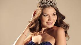 Mooie vrouw met donker haar in luxueuze kleding en het kostbare kroon stellen in studio stock video