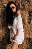 Mooie vrouw met donker haar in vrijetijdskleding, die op landbouwbedrijf stellen Royalty-vrije Stock Afbeeldingen
