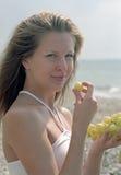 Mooie vrouw met druiven op strand royalty-vrije stock afbeelding
