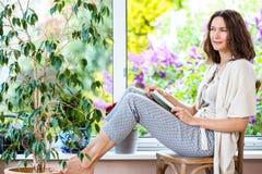 Mooie vrouw met een boek dichtbij het venster royalty-vrije stock fotografie